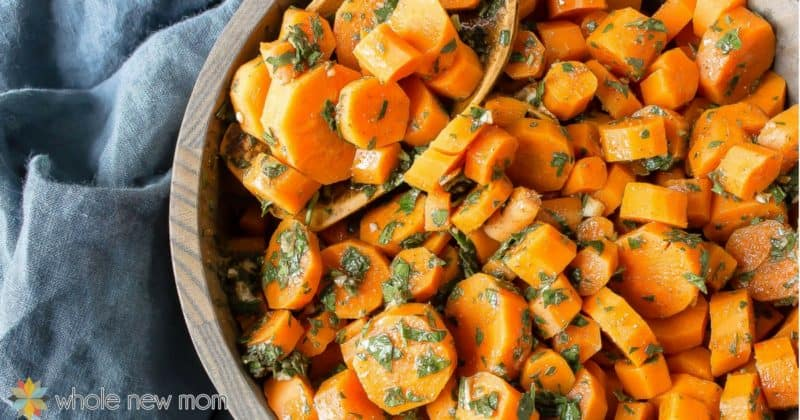 Sliced carrots in a bowl garnished with greens