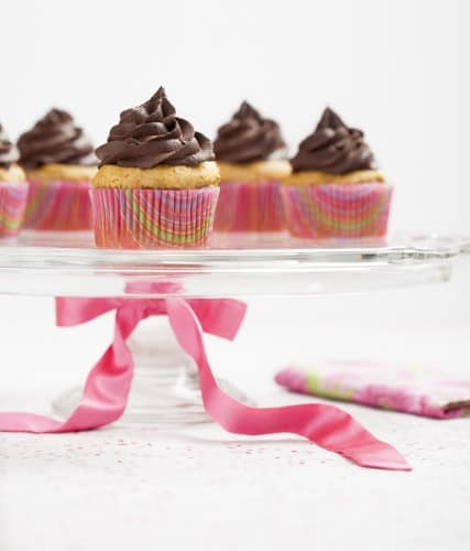 chocolate frosting on mini cupcakes in pink cupcake holders on a glass cake holder