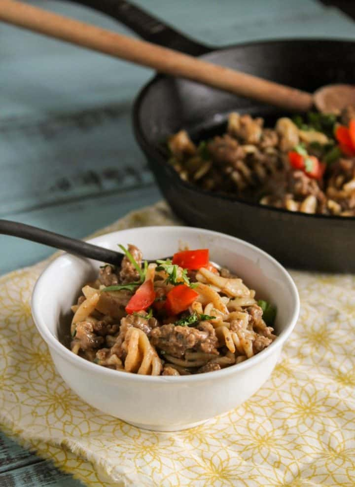 Healthy Hamburger Helper in a white bowl with cast iron skillet and wooden spoon in background