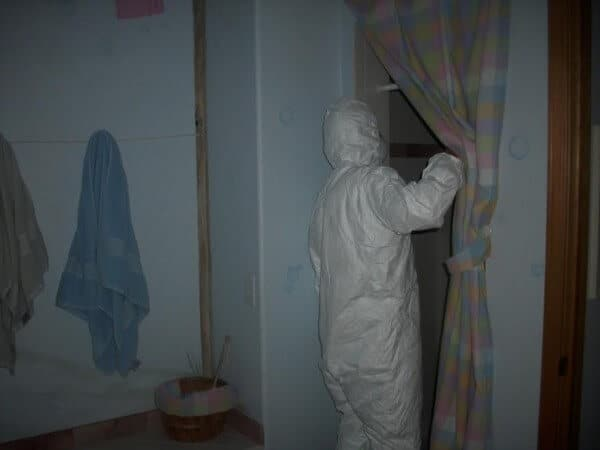 A Mold Inspector in Protective Gear in the Fabry's bathroom
