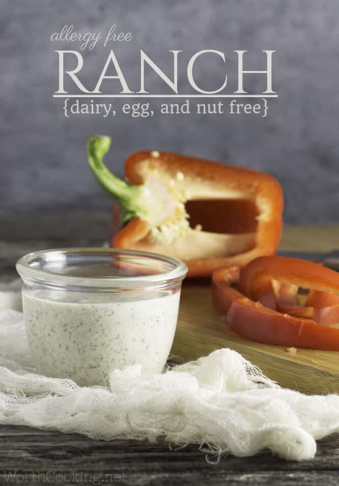 vegan ranch dressing in a glass container with cut up red peppers