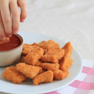 Hand dipping chicken nuggets in ketchup and a plate of chicken nuggets placed on top of a red and white checkered napkin