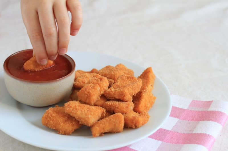 baked chicken nuggets on a white plate with hand dipping a nugget into ketchup