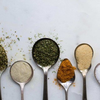 Several spoons lined up containing different spices