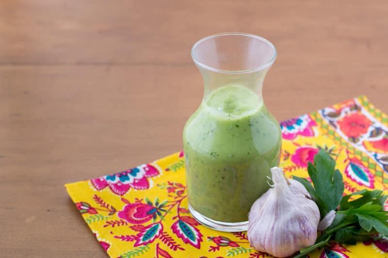 vegan avocado dressing in glass carafe on colored napkin