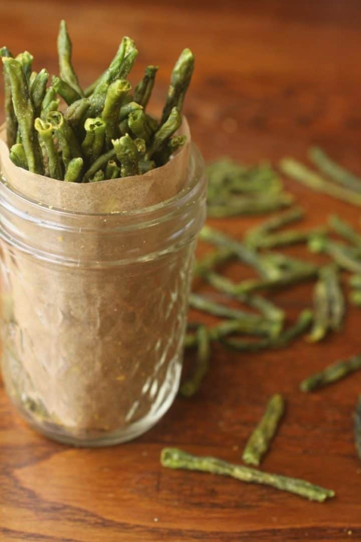 green bean chips in a glass jar on a wooden table