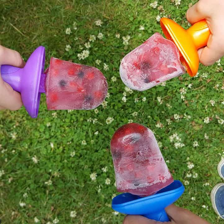 kids hands holding superfood berry popsicles