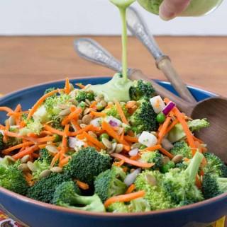 Pouring avocado dressing into broccoli salad
