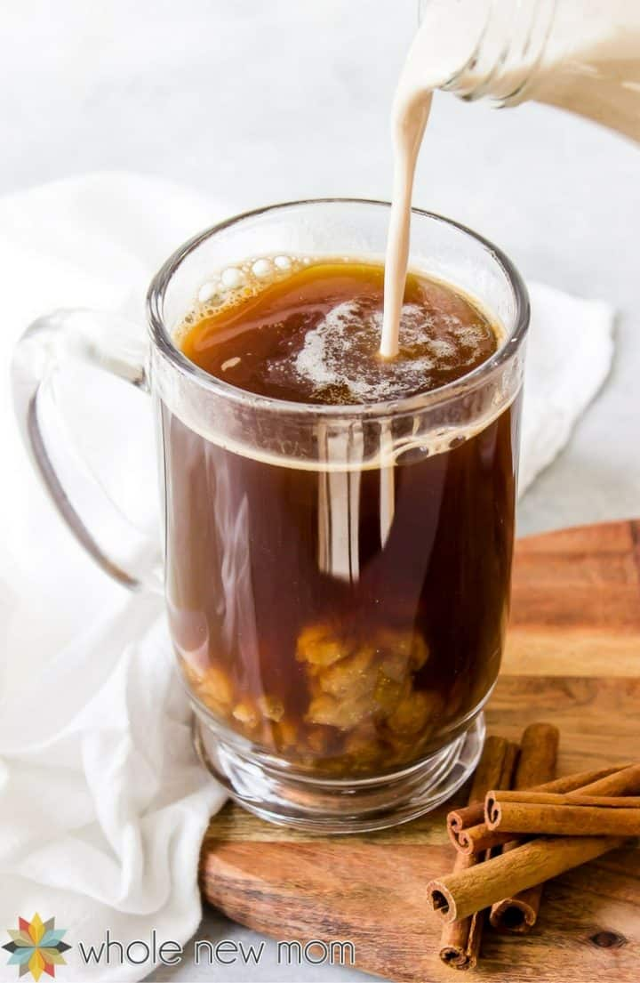 vegan pumpkin spice creamer being poured into a glass mug of coffee