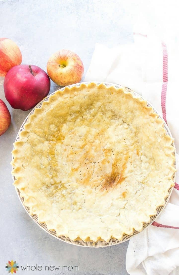 Baked pie crust in pie plate on top of white and red dish towel with two apples