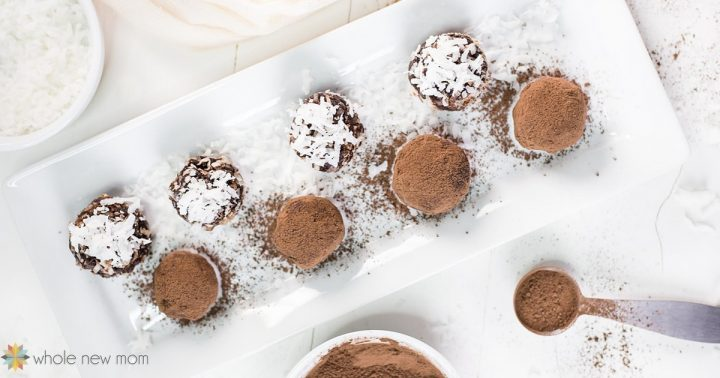 chocolate avocado truffles on a white rectangular serving plate with cocoa in a measuring spoon
