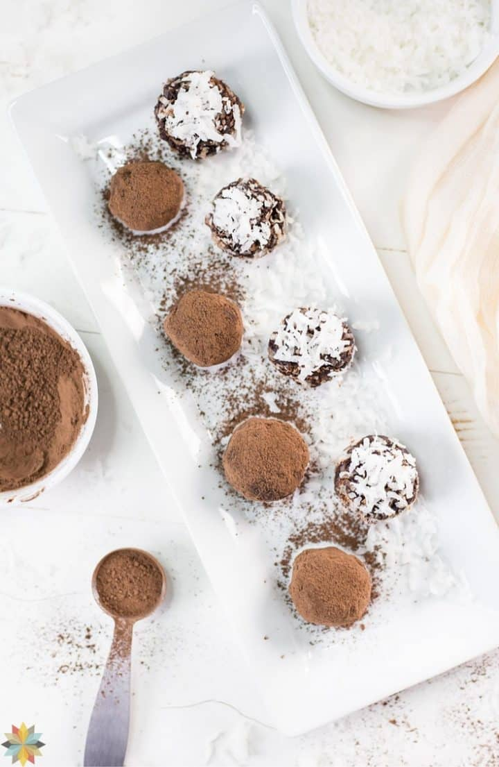 chocolate avocado truffles on a white rectangular serving plate with cocoa garnish in a measuring spoon