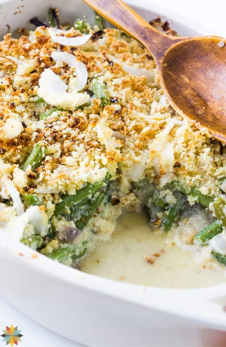 Gluten-free Green Bean Casserole in a white casserole dish with wooden spoon