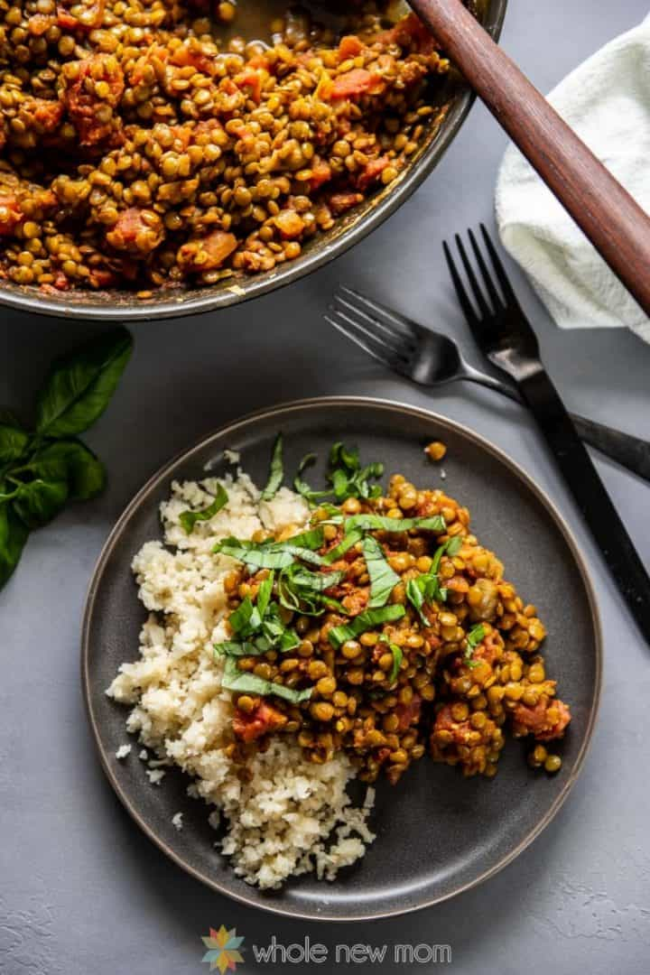 Indian Lentils on plate with Cauliflower Rice - next to serving bowl and 2 forks