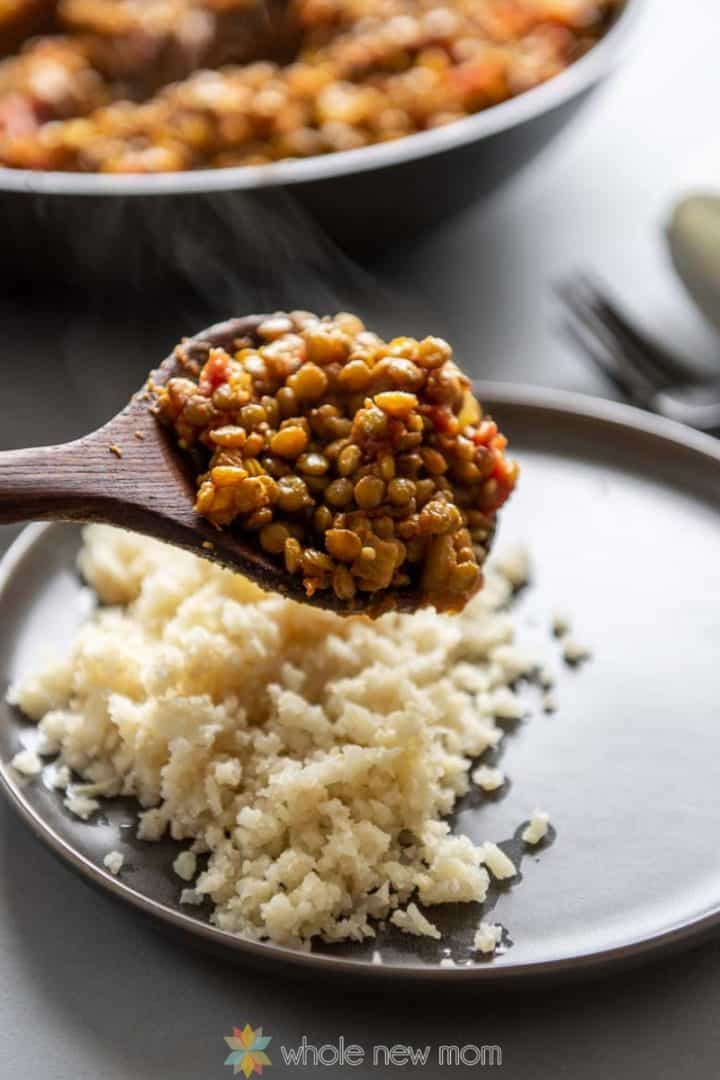 Indian Lentils in wooden serving spoon above plate of Cauliflower Rice