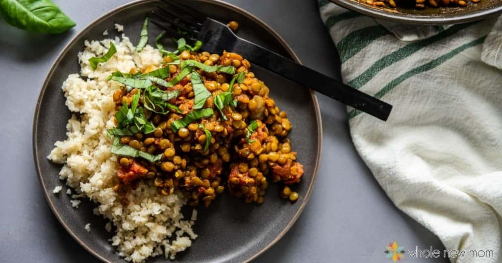 Indian lentil and cauliflower rice on a black plate with black fork