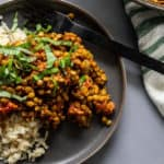 Indian Lentils on plate with Cauliflower Rice with black fork--on gray table with white cloth napkin