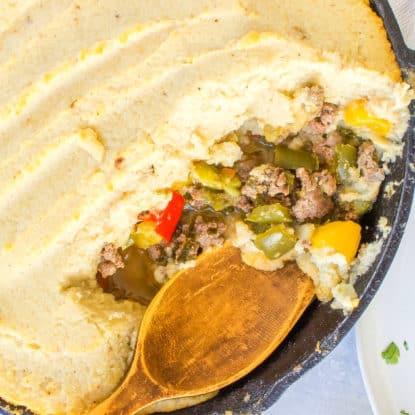 paleo shepherd's pie in cast iron skillet with wooden spoon