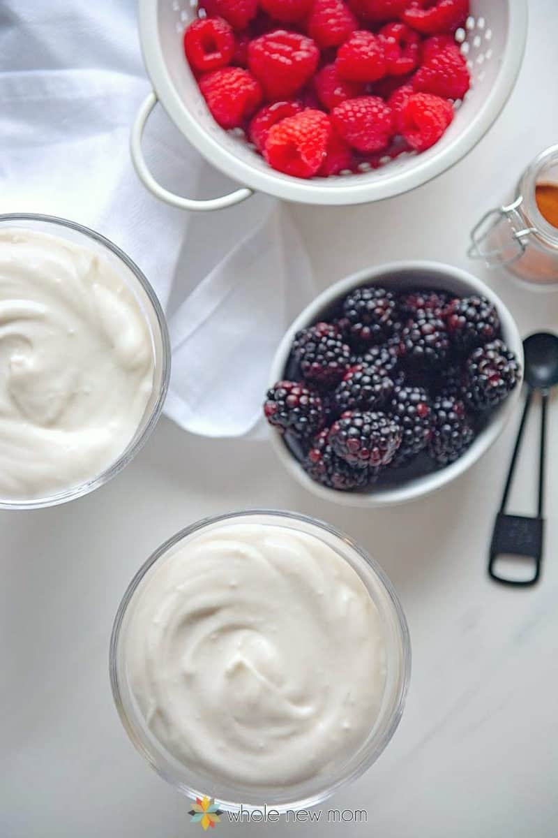 coconut milk pudding glass dessert cups with berries in white bowl and colander