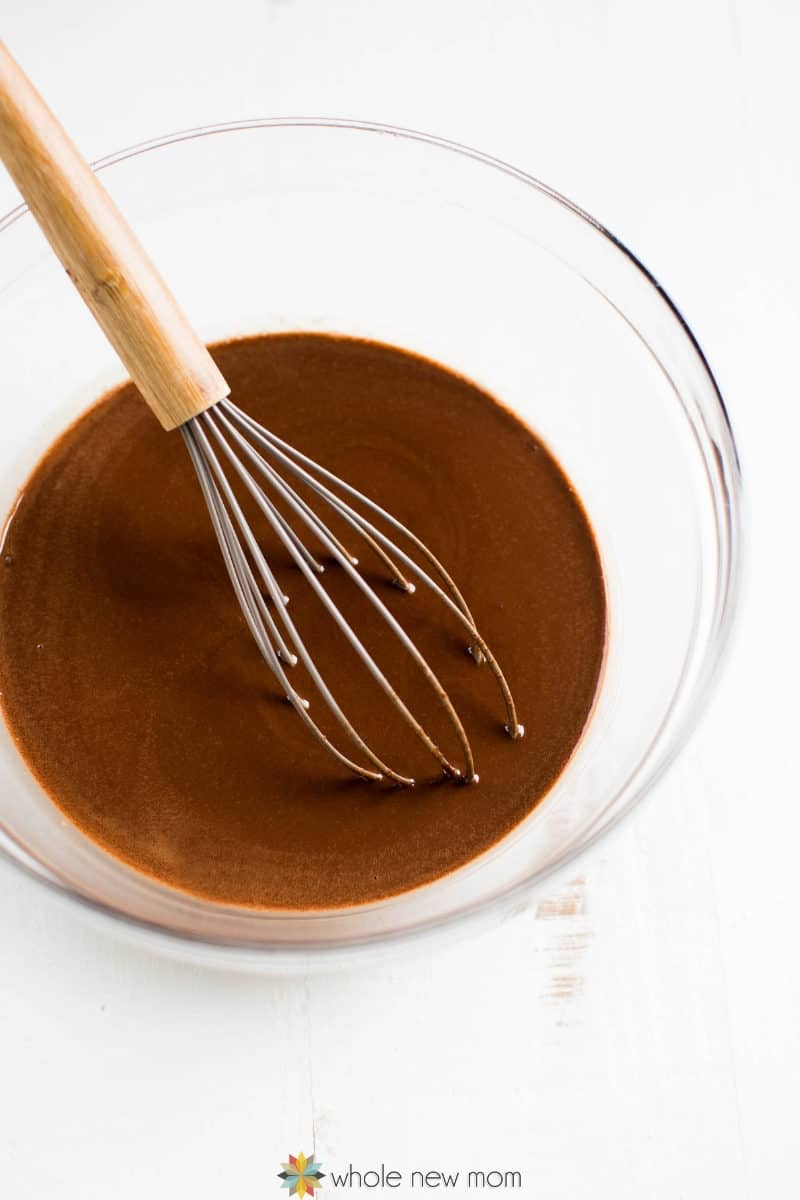 chocolate being whisked for paleo almond butter cups