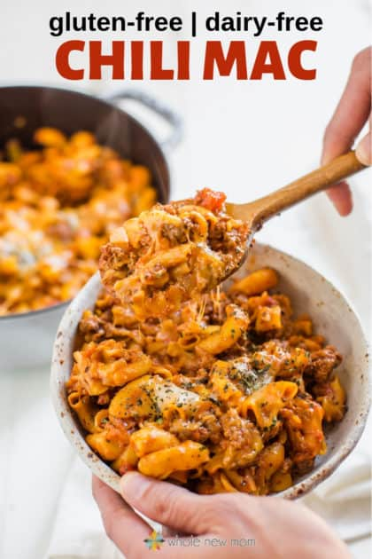 hands holding gluten free chili mac with dairy free cheese in bowl