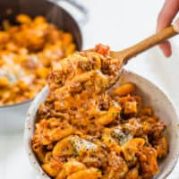 hands scooping gluten free chili mac into bowl with wooden spoon