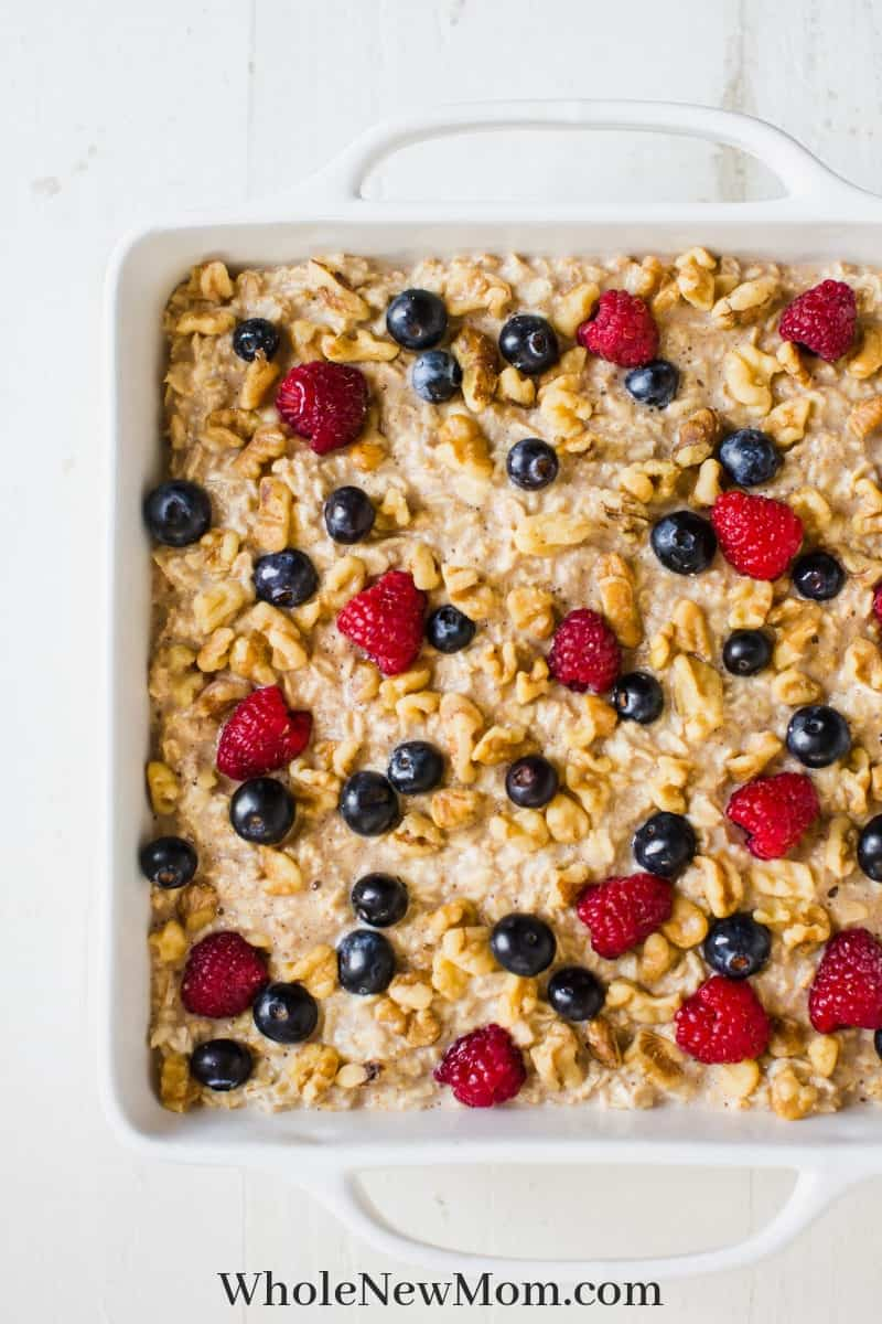 Baked oatmeal cake topped with berries and walnuts in a white baking pan