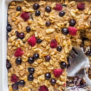gluten free oatmeal cake with berries in a white baking pan