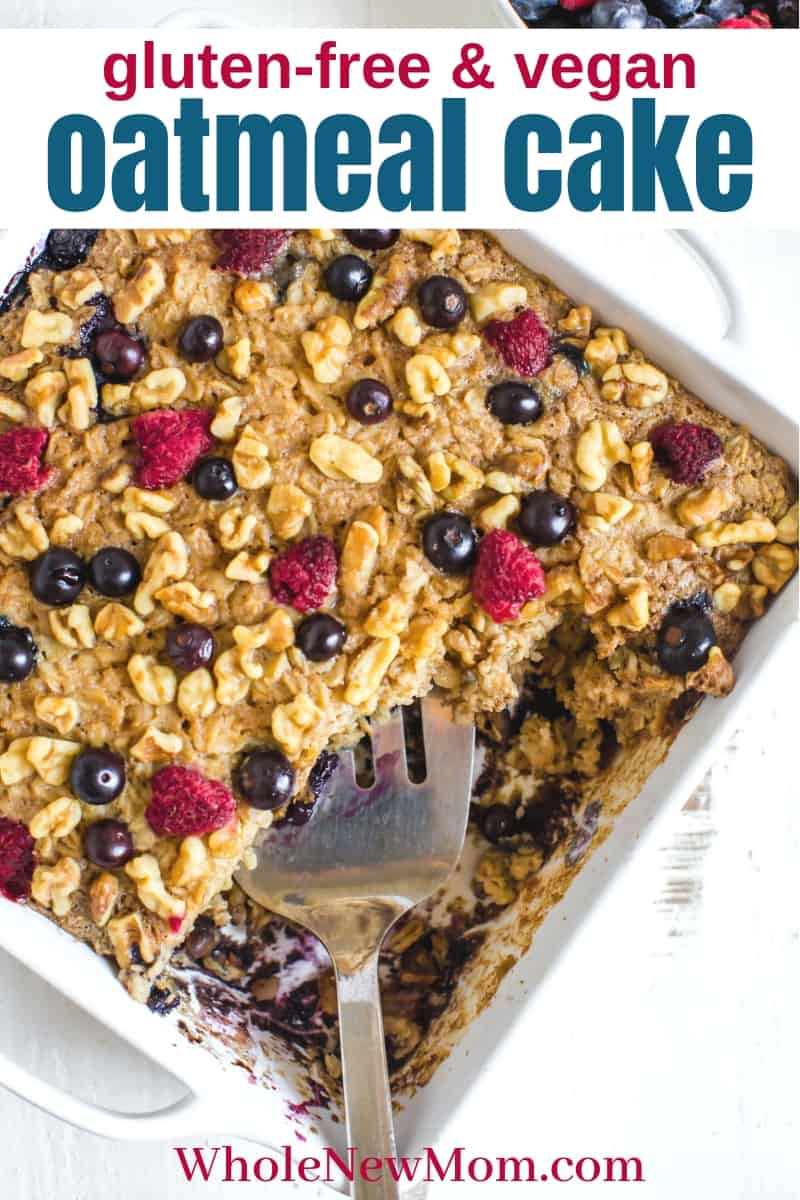 gluten-free oatmeal cake with berries on top in white pan with spatula