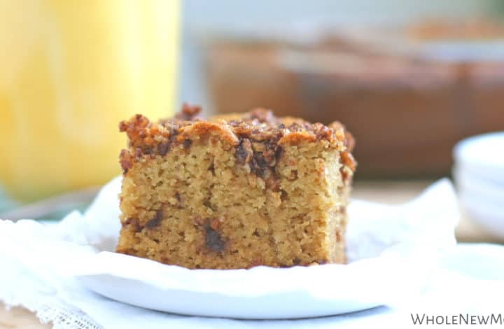 paleo coffee cake on white plate with yellow mug in background