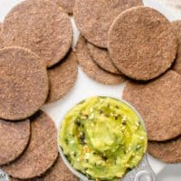 lentil crackers with guacamole in a small metal bowl