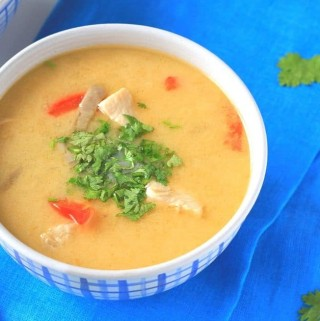 thai chicken soup in a white and blue bowl with spoons