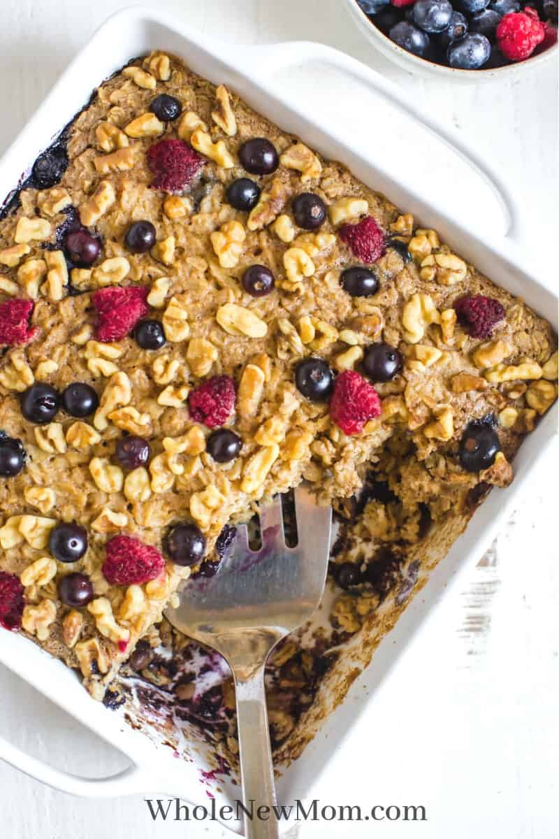 vegan oatmeal cake with berries on top in white pan with spatula