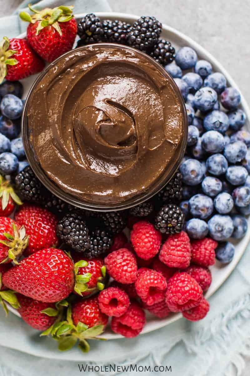 healthy chocolate fruit dip in a small glass bowl surrounded by fresh berries