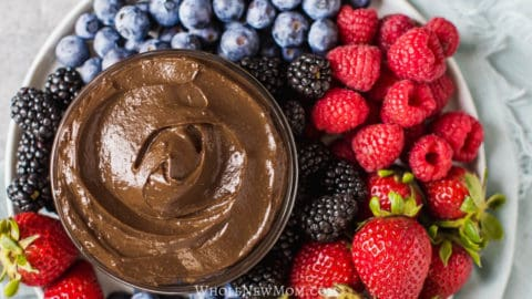healthy chocolate dip in a glass bowl surrounded by fresh berries