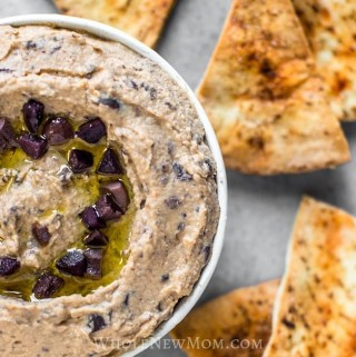 olive hummus in white bowl with baked pita bread wedges