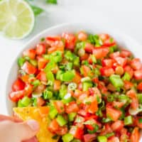 hand dipping tortilla chip into fresh salsa in white bowl