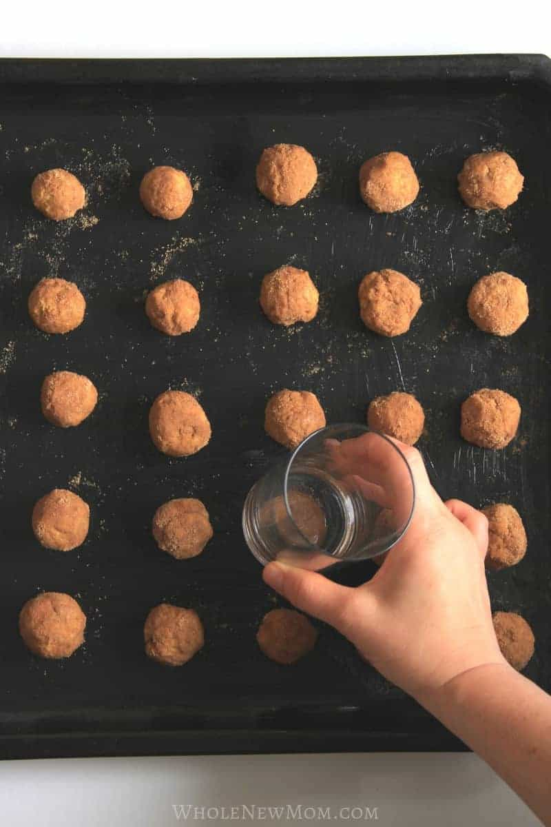 using a glass to flatten pumpkin snickerdoodle dough balls on a baking sheet