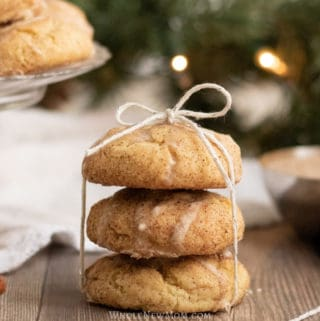 Stack of three gluten-free egg nog cookies tied by a thin white ribbon and a plate of the same cookies behind it