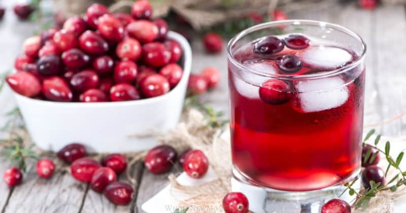 homemade cranberry juice in a glass with white bowl filled with cranberries