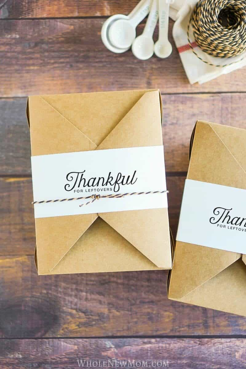 A portrait of Thankful for leftovers label over a brown paper box placed on top of a wooden table