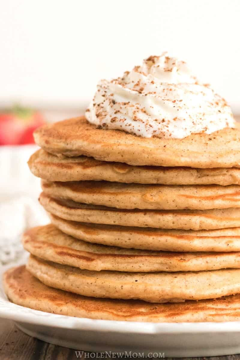 gluten-free eggnog pancakes on white plate with whipped cream and nutmet