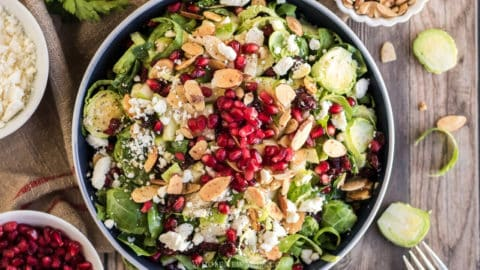 shaved brussels sprout salad with cranberries, almonds, and pomegranates