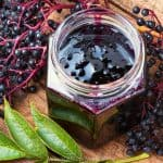 homemade elderberry jam on a wooden table with elderberries and leaves surrounding the jar