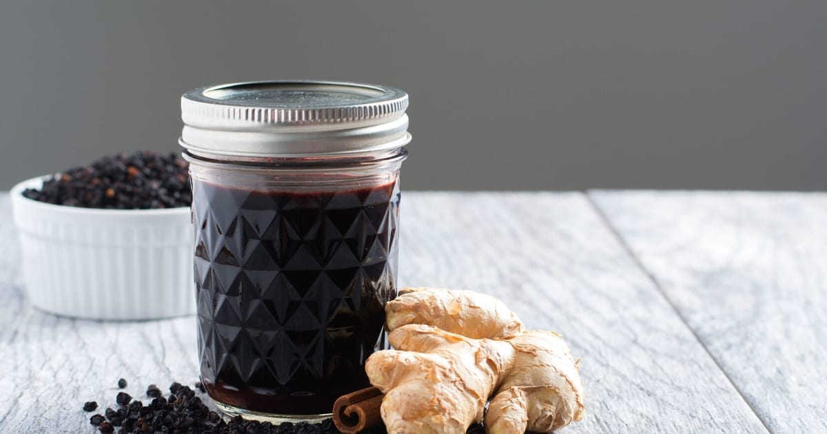 homemade elderberry syrup in a glass jelly mason jar wit cinnamon and ginger