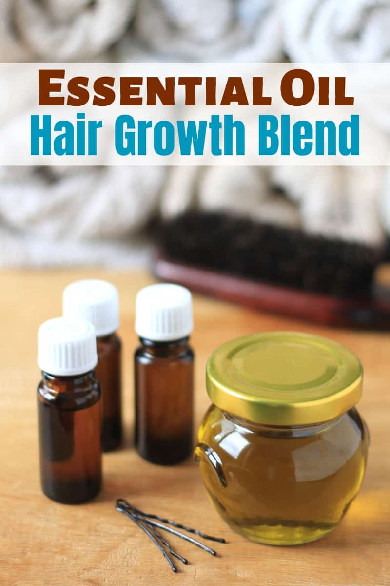 DIY Essential Oil Blend for Hair Growth in a jar with a brush and bobby pins and essential oil bottles