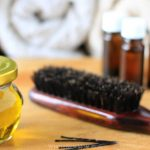essential oil in a small glass jar and a brown hair brush and three small amber bottles on the background