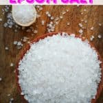Epsom salt in a wooden bowl and spoon on a wooden table for post about epsom salt uses