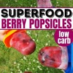 Kids holding homemade superfood berry popsicles with grass in the background