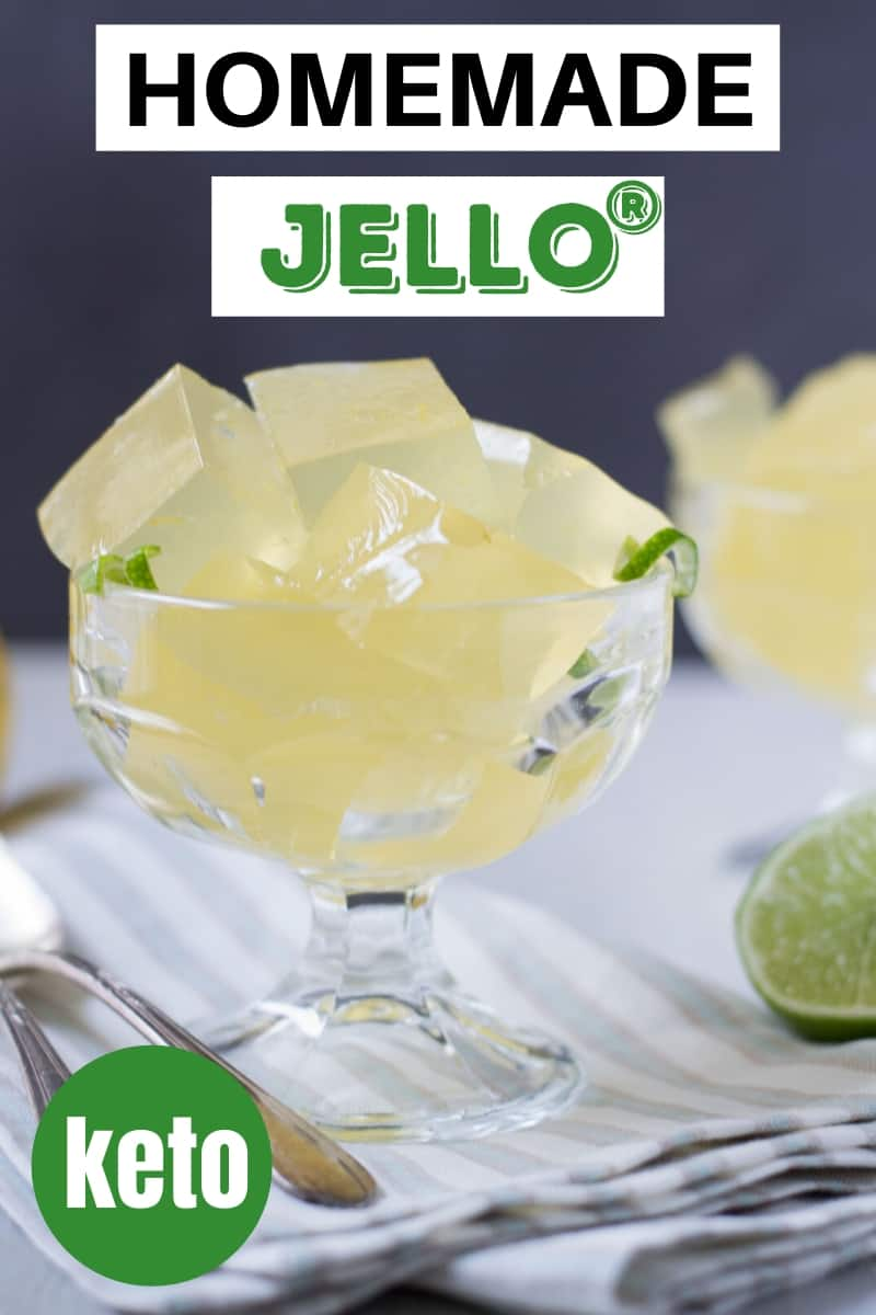 homemade jello in a glass dish with spoons resting on the table and half a lime on the table